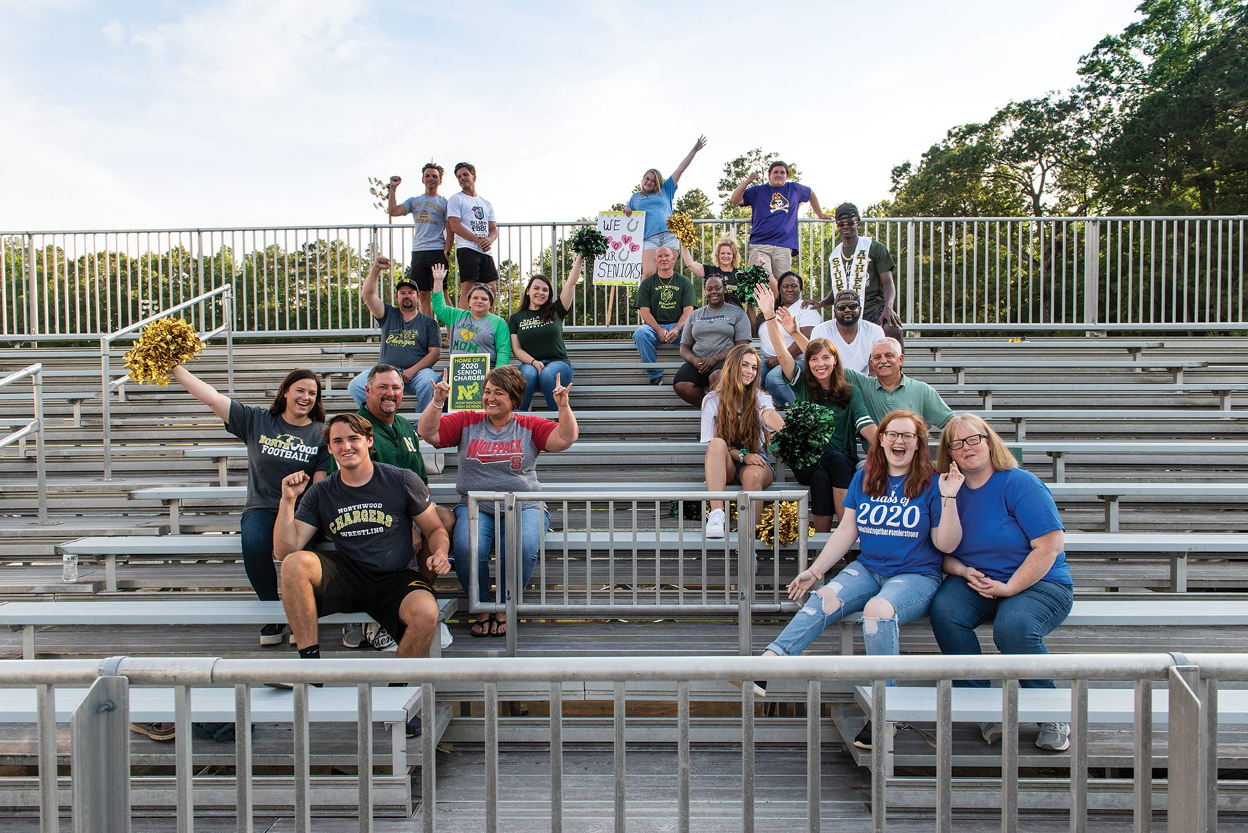 Adopted high school seniors sit with their families on the bleachers of Northwood High School